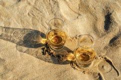 Exponeringsglas av enkel malt för whisky på sandstranden, ett exponeringsglas av tasti Royaltyfri Foto