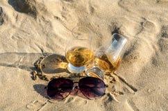 Exponeringsglas av enkel malt för whisky på sandstranden, ett exponeringsglas av tasti Royaltyfri Fotografi
