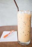 Exponeringsglas av förkylning mjölkar kaffe på trätabellen Arkivfoto