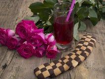 Exponeringsglas av fruktsaft med en bukett av rosor och kakor Arkivfoton
