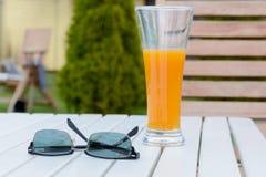 Exponeringsglas av fruktsaft och solglasögon på tabellen Fotografering för Bildbyråer