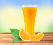 Exponeringsglas av fruktsaft, orange skiva med sidor på trätabellen över na Royaltyfria Bilder