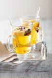Exponeringsglas av funderad äppelcider med apelsinen och kryddor, vinterdrin arkivbild