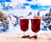 Exponeringsglas av funderat vin över vinterlandskap Arkivfoto