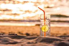 Exponeringsglas av Gin Tonic med sugrör- och limefruktskivan på stranden, på solnedgången Long Beach Ko Lanta, Thailand arkivfoton