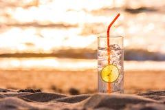 Exponeringsglas av Gin Tonic med sugrör- och limefruktskivan på stranden, på solnedgången Long Beach Ko Lanta, Thailand arkivfoto