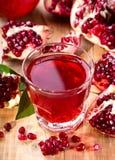Exponeringsglas av granatäpplefruktsaft med nya frukter Arkivbilder