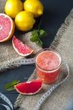 Exponeringsglas av grapefruktfruktsaft och mätabandet Royaltyfria Bilder
