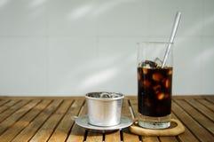 Exponeringsglas av iskaffe & det vietnamesiska traditionella kaffefiltret på wo Arkivfoto