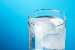 Exponeringsglas av isvatten på blå bakgrund Arkivfoto