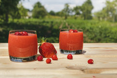 Exponeringsglas av jordgubbesmoothien på trätabellen med mintkaramellen arkivfoton