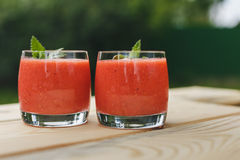 Exponeringsglas av jordgubbesmoothien på trätabellen med mintkaramellen Arkivfoto