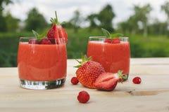 Exponeringsglas av jordgubbesmoothien på trätabellen med mintkaramellen royaltyfria bilder