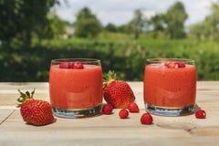Exponeringsglas av jordgubbesmoothien på trätabellen med mintkaramellen Fotografering för Bildbyråer