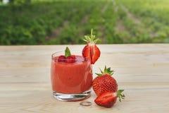 Exponeringsglas av jordgubbesmoothien på trätabellen med mintkaramellen royaltyfri fotografi