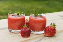 Exponeringsglas av jordgubbesmoothien på trätabellen med mintkaramellen Arkivbild