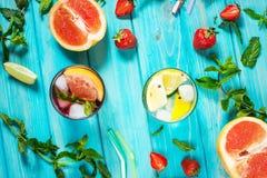 Exponeringsglas av kall coctail för alkohol dekorerade med is, frukt och mintkaramellen som blir på den wood tabellen Ny fruktsaf royaltyfri fotografi