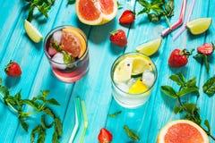 Exponeringsglas av kall coctail för alkohol dekorerade med is, frukt och mintkaramellen som blir på den wood tabellen Ny fruktsaf royaltyfri bild