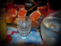 Exponeringsglas av av kall vodka mot en bakgrund av smörgåsar med laxen Karaff med vodka Naturlig mat, aptitretare arkivbilder