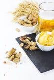 Exponeringsglas av kallt öl med chiper och jordnötter som isoleras på vitbaksida Royaltyfri Bild