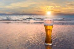 Exponeringsglas av kallt öl på havskusten på solnedgången Koppla av på stranden royaltyfria bilder
