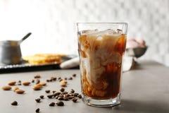 Exponeringsglas av kallt kaffe med bönor och muttrar royaltyfria bilder