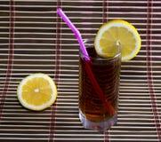 Exponeringsglas av kallt svart te med en citron Arkivfoto