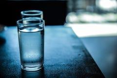 Exponeringsglas av kallt vatten på den svarta tabellen Fotografering för Bildbyråer