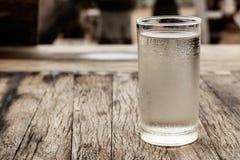 Exponeringsglas av kallt vatten på en tabell fotografering för bildbyråer