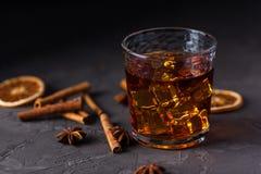 Exponeringsglas av konjak eller whisky, kryddor och garneringar p? m?rk bakgrund S?songsbetonat feriebegrepp arkivbild