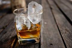 Exponeringsglas av kväv whisky med is royaltyfri bild