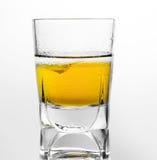 Exponeringsglas av kväv whisky och is på en vit bakgrund royaltyfri bild