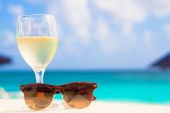 Exponeringsglas av kyld vitt vin och solglasögon på Arkivfoton