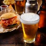 Exponeringsglas av kylt öl med en hamburgare arkivfoton
