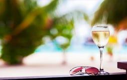 Exponeringsglas av kylt vitt vin på tabellen nära stranden Arkivfoton