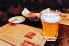 Exponeringsglas av öl på tabellen i bar arkivfoton