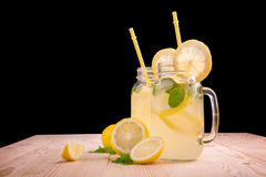 Exponeringsglas av lemonad med gula sugrör med sidor och limefrukter för ny mintkaramell, saftiga citroner och mineralvatten på e Royaltyfria Foton
