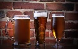Exponeringsglas av ljus öl på en mörkerpub. Royaltyfria Bilder