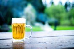 Exponeringsglas av ljust öl med skum på en trätabell Trädgårds- parti Naturlig bakgrund _ Utkastöl royaltyfri bild