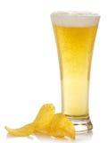 Exponeringsglas av ljust öl och de guld- chiperna royaltyfri bild