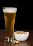 Exponeringsglas av ljust öl och pistaschen i en bunke royaltyfria bilder