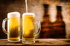 Exponeringsglas av ljust öl på en träbakgrund med skugga av två bo fotografering för bildbyråer