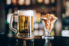 Exponeringsglas av ljust kallt skummigt öl, muttrar i bar arkivfoto