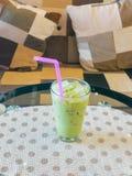 Exponeringsglas av med is grönt te på tabellen Arkivfoto