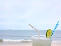 Exponeringsglas av med is lemonad på stranden arkivfoton
