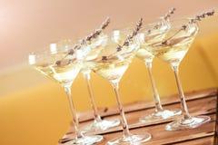 Exponeringsglas av med vit champagne dekorerade med lavendel Arkivfoton
