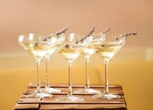 Exponeringsglas av med vit champagne dekorerade med lavendel Fotografering för Bildbyråer