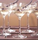 Exponeringsglas av med vit champagne dekorerade med lavendel Arkivfoto
