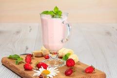 Exponeringsglas av milkshaken med mintkaramellen och nya jordgubbar, banan på Royaltyfri Foto