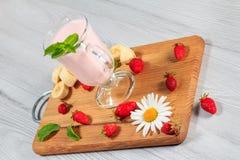 Exponeringsglas av milkshaken med mintkaramellen och nya jordgubbar, banan på Royaltyfria Bilder